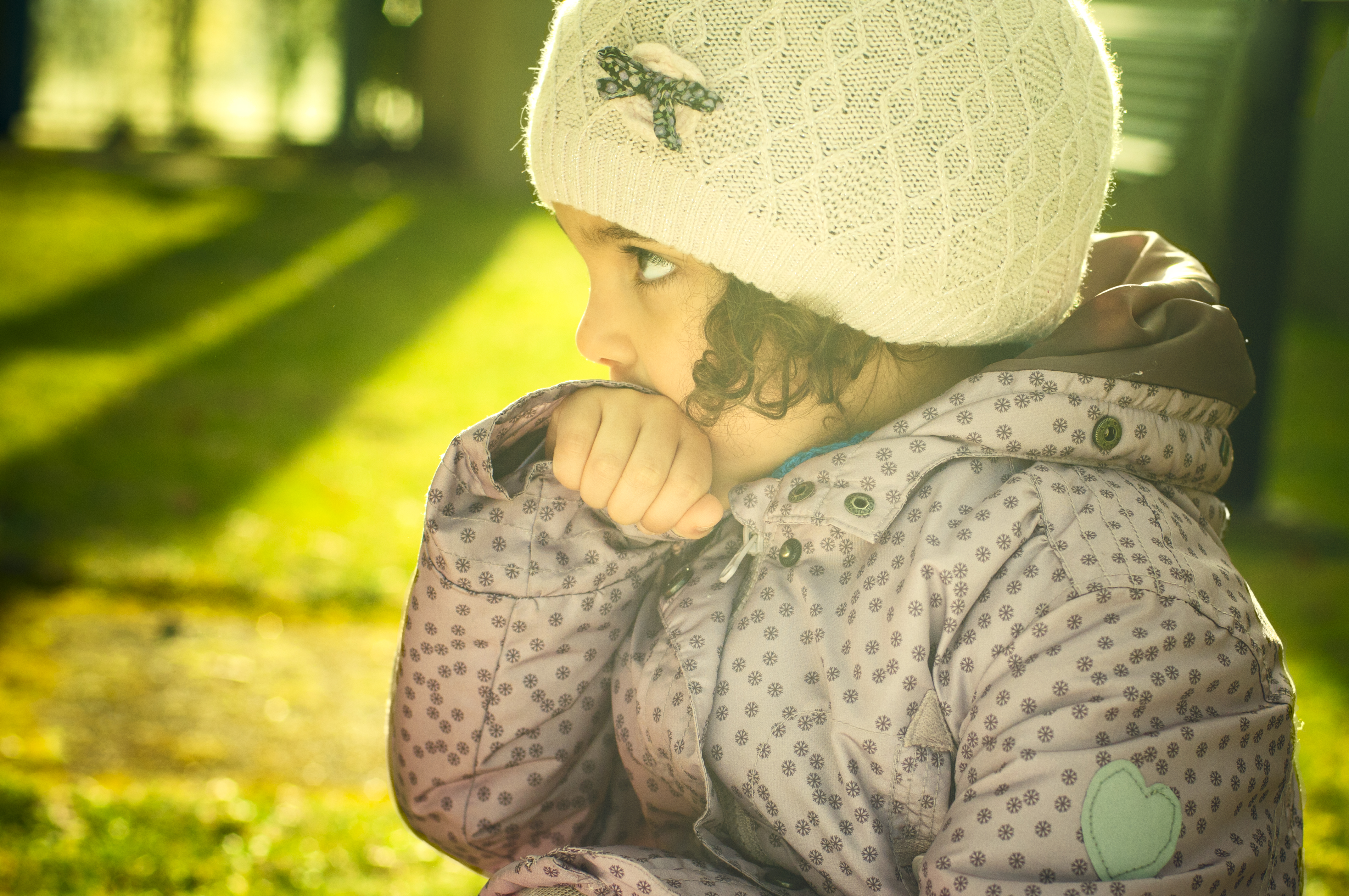 young girl biting on coat